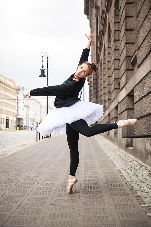 Sesja baletowa w centrum miasta, tancerka w pointach stoi z uniesioną nogą