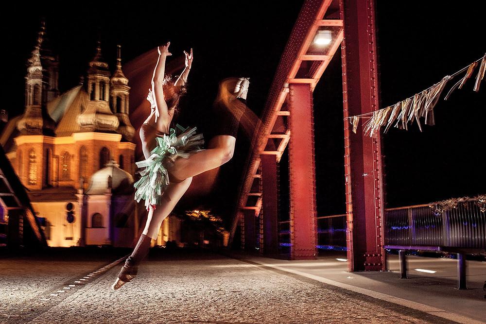 Tancerka baletu skacze na tle katedry w Poznaniu