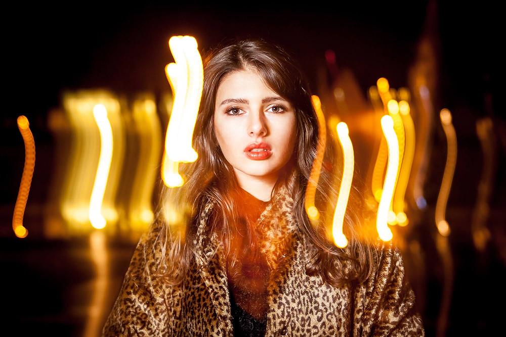 Poruszone pionowo światła, portret modelki w płaszczu w panterkę, kreatywna sesja portretowa Poznań