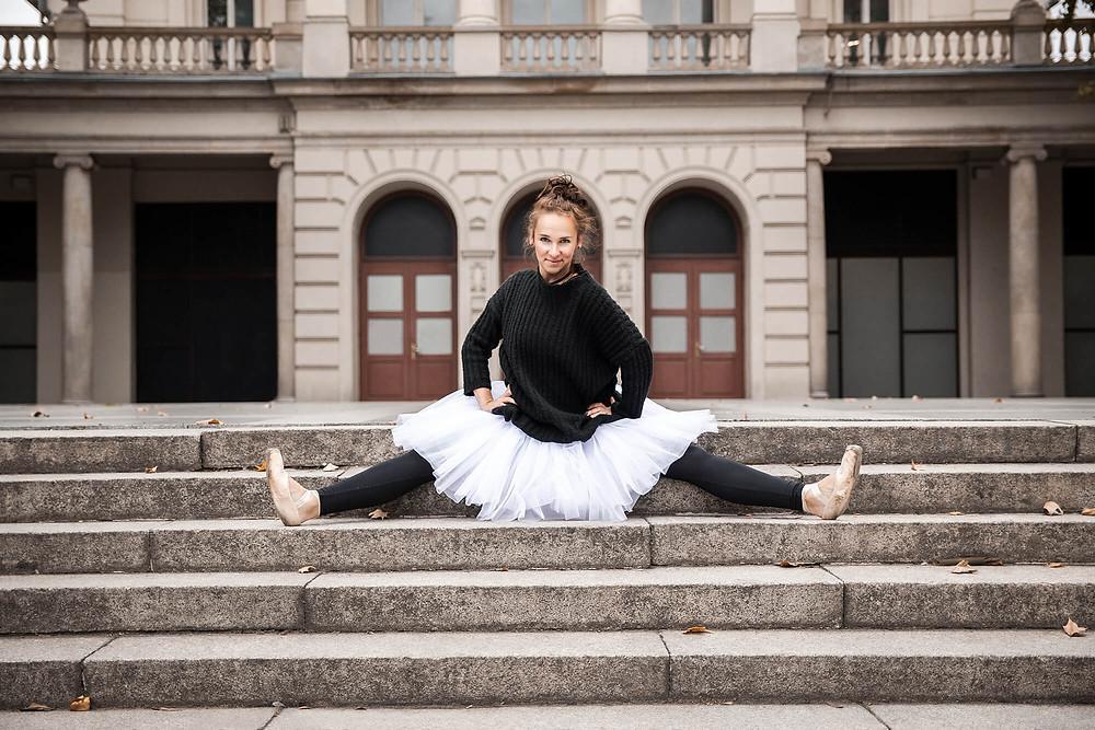 Uśmiechnięta baletnica siedzi na schodach