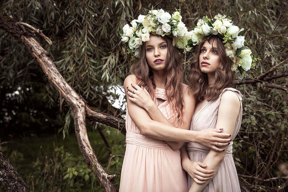Sesja edytorial, leśne nimfy, dwie modelki w długich pastelowych sukniach z kwiatami na głowie