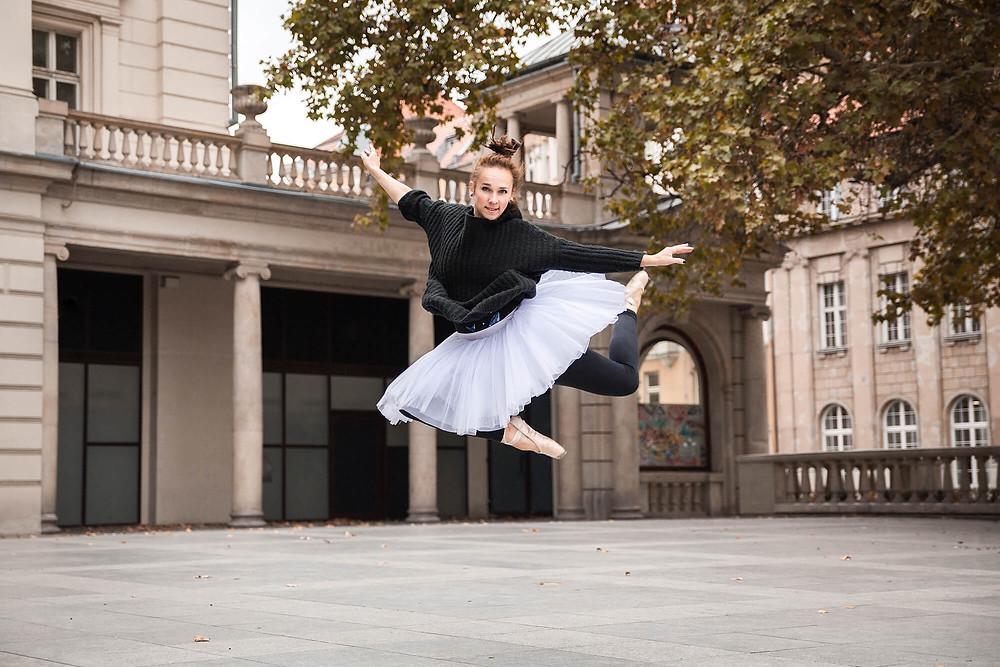 Baletnica w skoku na tle zabytkowych budynków