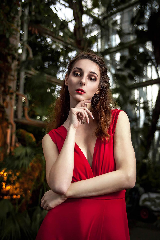 Portret modelki w czerwonej sukni na tle szklanej ściany palmiarni