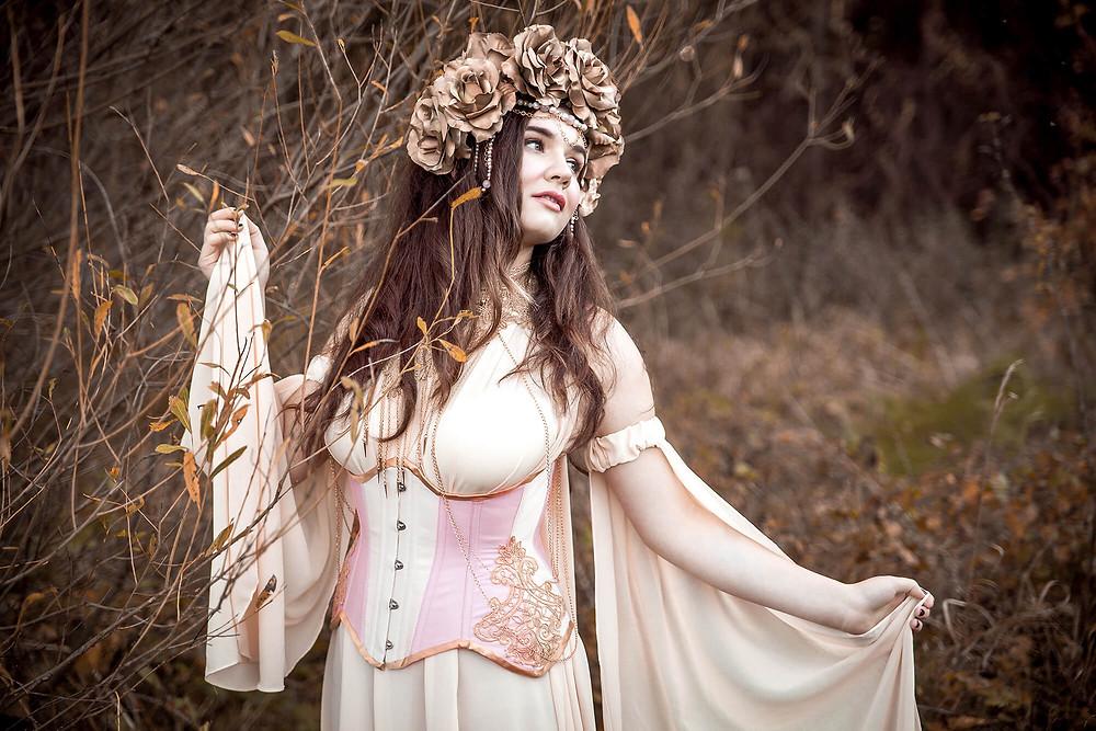 Fantazyjna sesja zdjęciowa, baśniowa suknia, korona z róż, modelka ogląda się za siebie