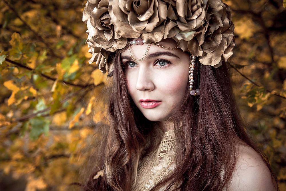 Dziewczyna patrzy w dal w opasce ze złotych róż, fantazyjna stylizacja do sesji zdjęciowej