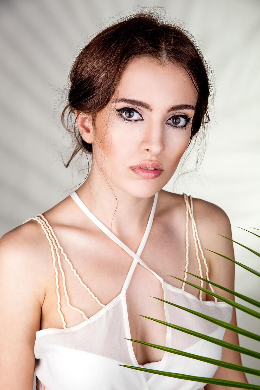 Modelka z mocnymi oczami pozuje przysłonięta liściem