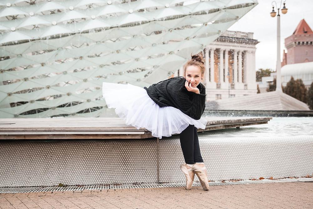 Uśmiechnięta baletnica siedzi przy fontannie w Poznaniu