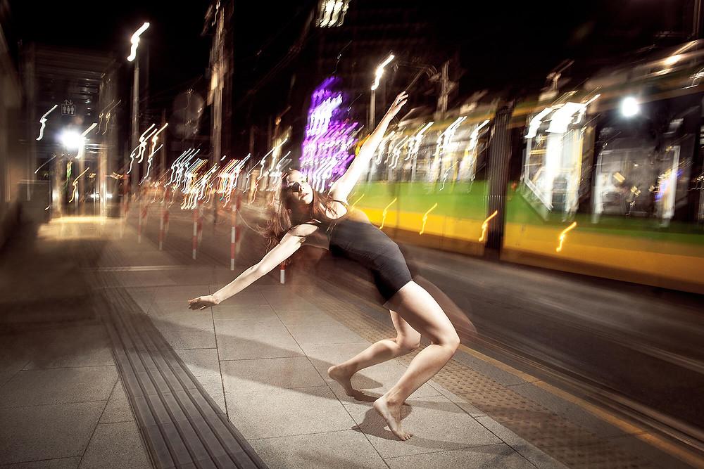 Tancerka contemporary w dynamicznej pozie na tle rozświetlonej ulicy