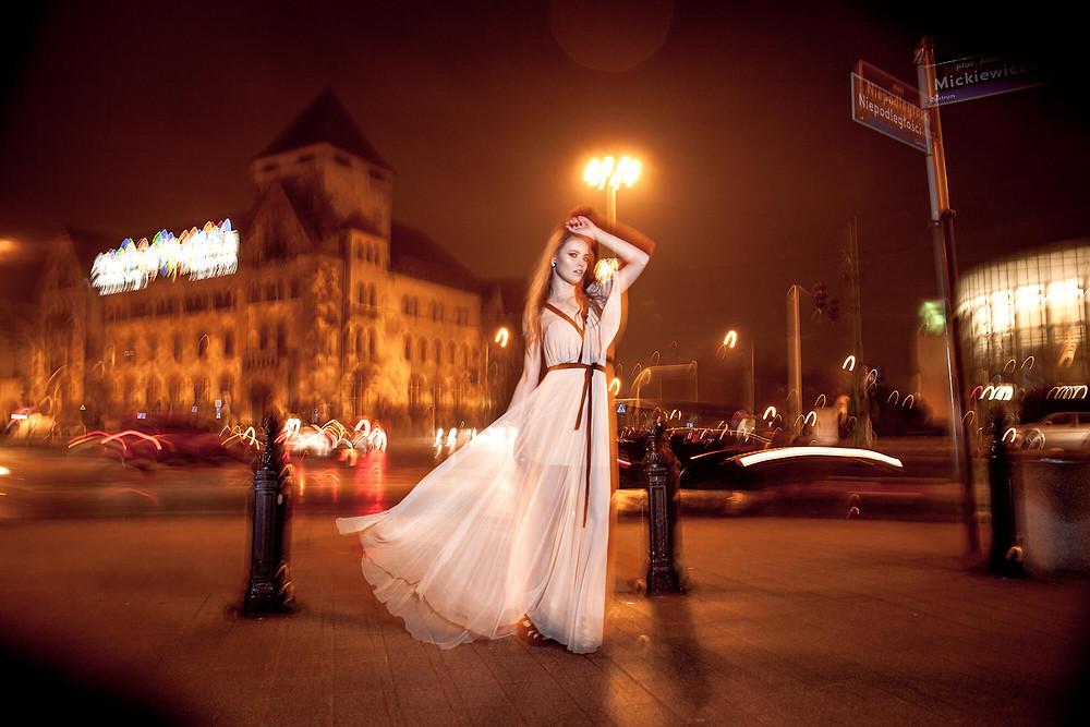 Nocny edytorial z ruchem ulicznym w tle i elegancką kreacją na pierwszym planie