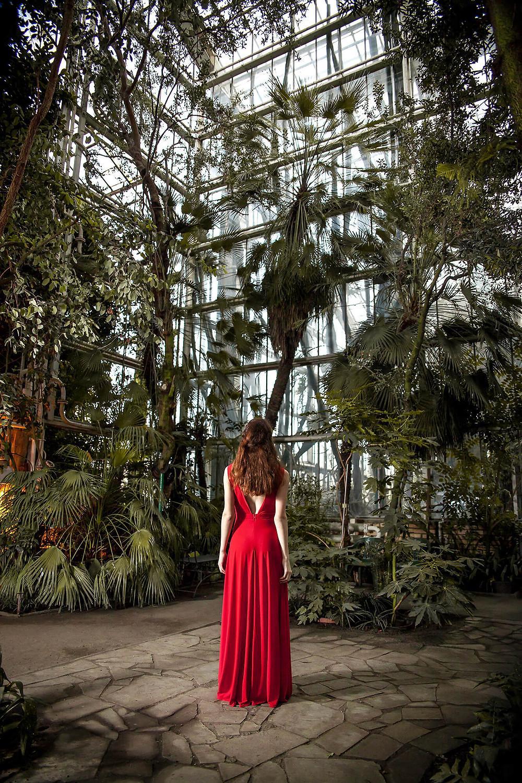 Szerokie ujęcie, modelka stoi tyłem w długiej sukni w palmiarni