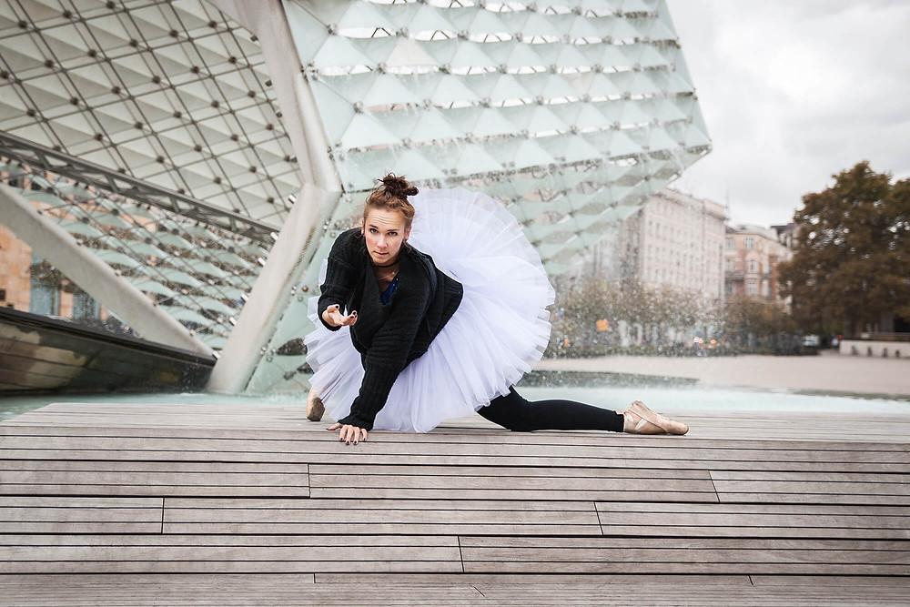 Tancerka w baletowej paczce na tle szklanej fontanny