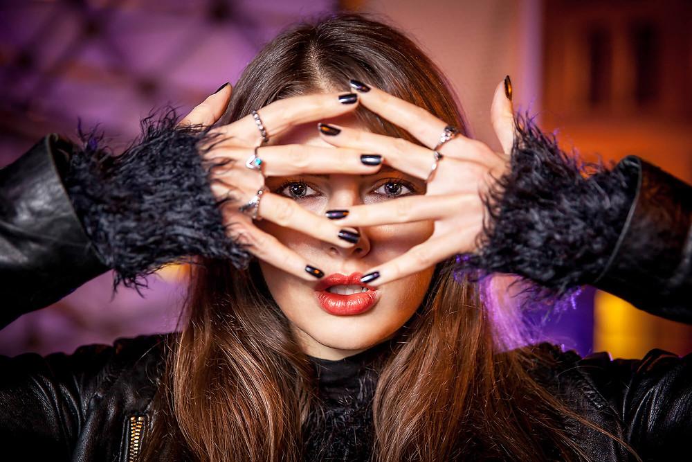 Centralny portret, oczy modelki widoczne między palcami, kreatywna fotografia portretowa w Poznaniu