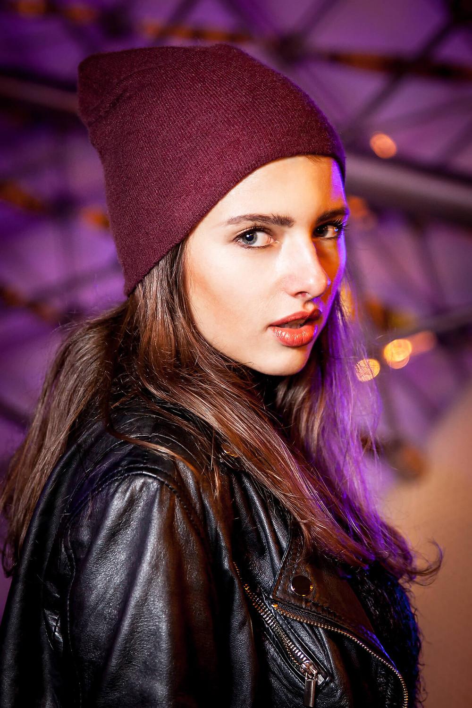 Portret na tle rozświetlonej na fioletowo fontanny, piękna dziewczyna  w czapce obraca się do obiektywu, fotograf mody Poznań