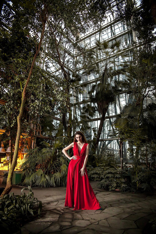 Egzotyczna sesja fashion w palmiarni, długa czerwona suknia i wysokie szklane wnętrze