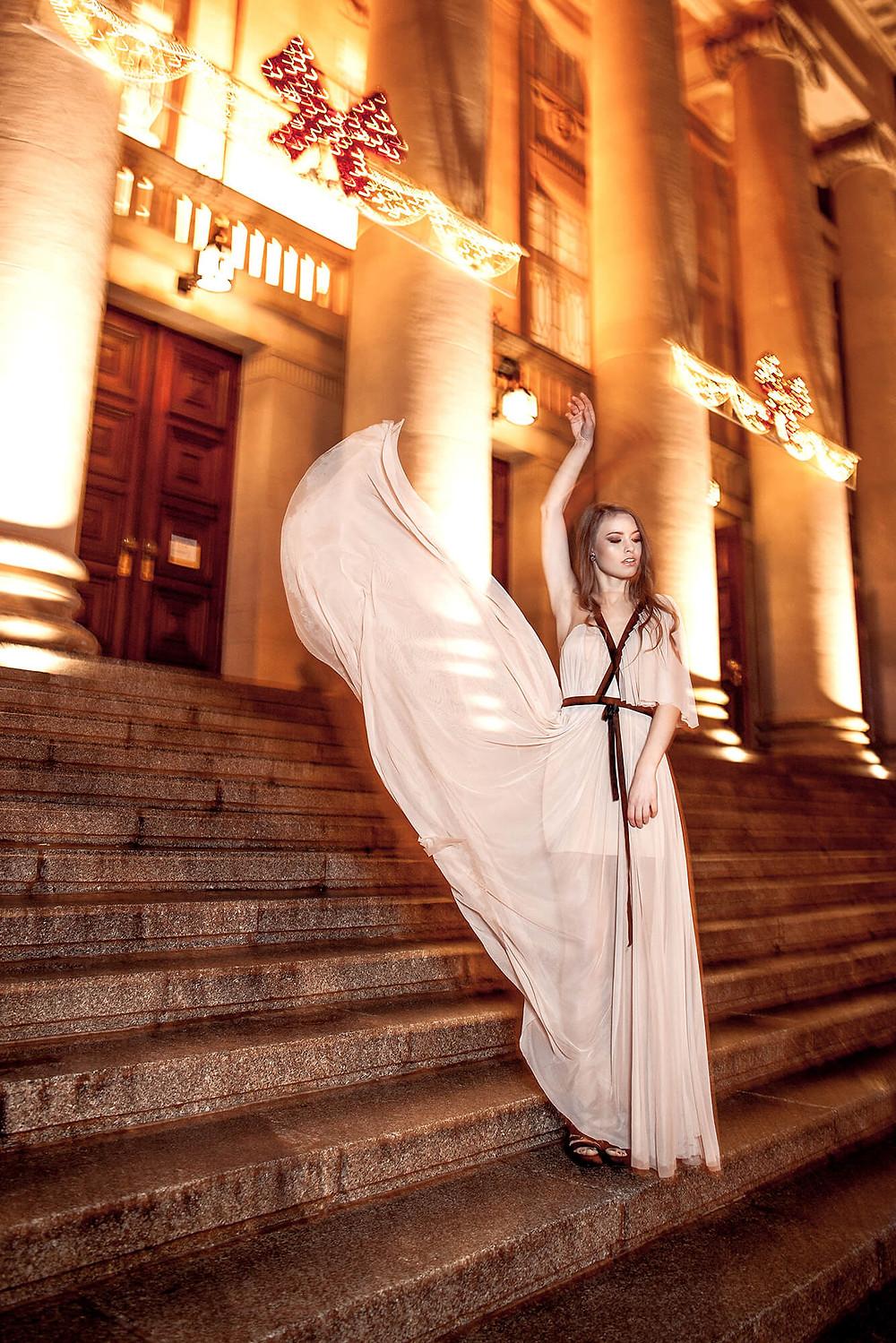 Modelka prezentuje zwiewną kreację na tle Opery