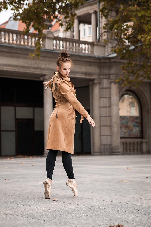 Baletnica w ręcznie malowanym, camelowym płaszczu stoi en pointe