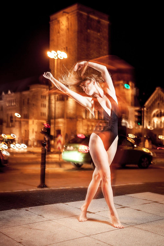 Dziewczyna tańczy na ulicy, poznański Zamek w tle