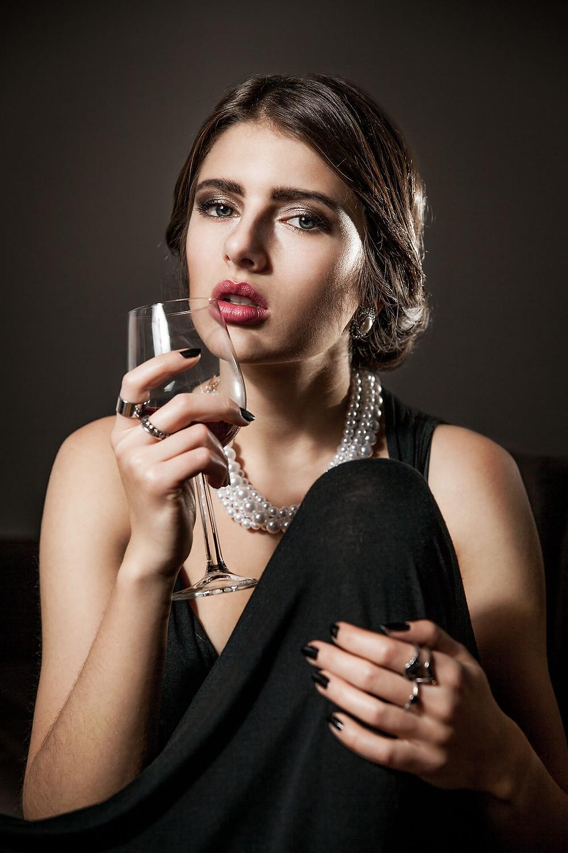 Wytworna kobieta trzymająca w dłoni kieliszek czerwonego wina, wieczorowa suknia i perły, sesja zdjęciowa w domu Poznań