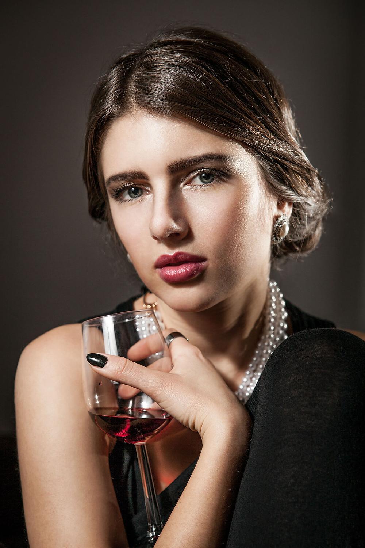 Portret kobiety z kieliszkiem czerwonego wina, subtelna fotografia portretowa