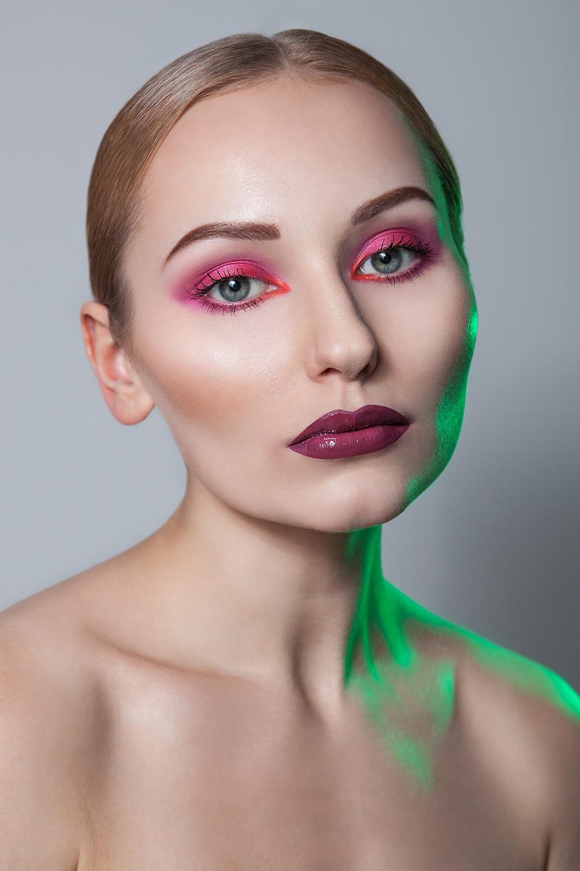Sesja beauty z różowym makijażem i zielonym światłem