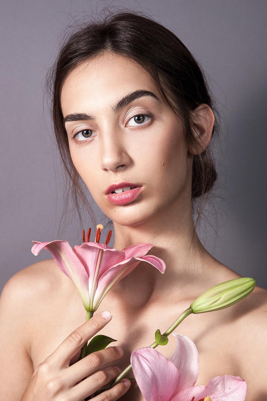 Modelka no make up trzyma różową lilię