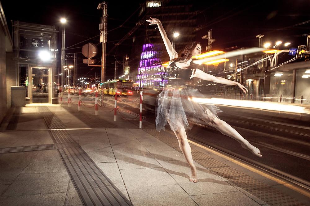 Off balance, tancerka z wyciągniętymi rękami patrzy za odjeżdżającym nocnym tramwajem