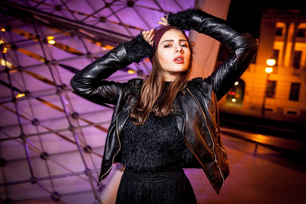 Sesja zdjęciowa fashion w Poznaniu, nocna sesja fashion, modelka eksponuje skórzaną kurtkę na tle nowoczesnej fontanny