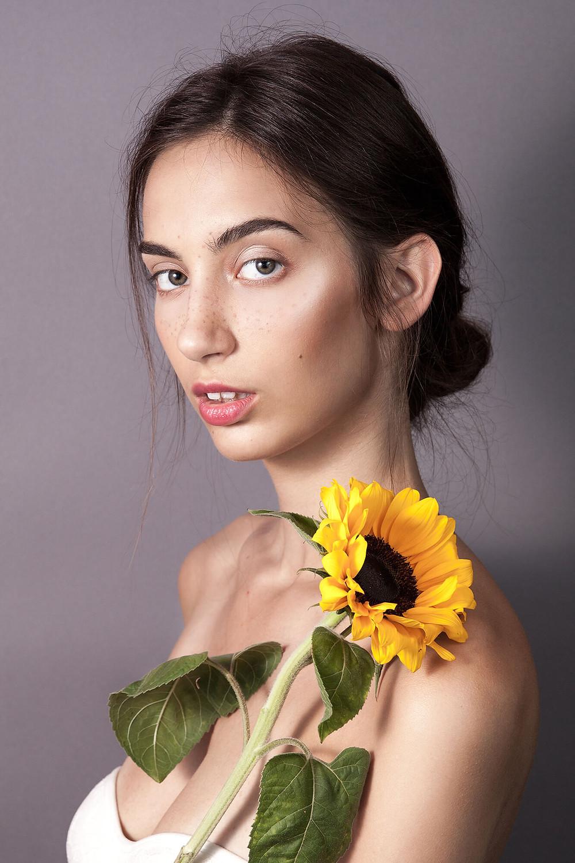 Piękna modelka w delikatnym makijażu pozuje ze słonecznikiem