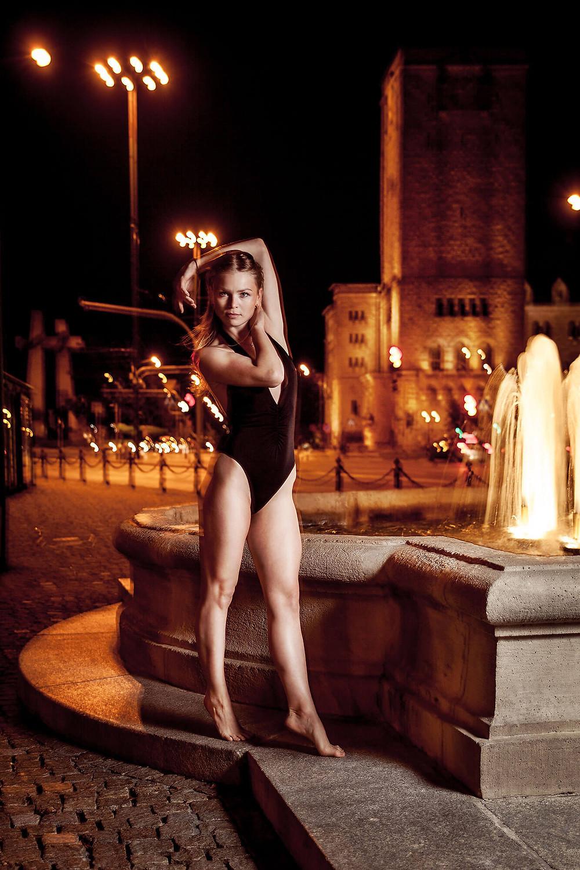 Tancerka w statycznej pozie przy fontannie, w tle Zamek Cesarski w Poznaniu