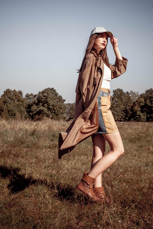 Modelka w brązowym prochowcu i czapce z daszkiem pewnie idzie przez łąkę