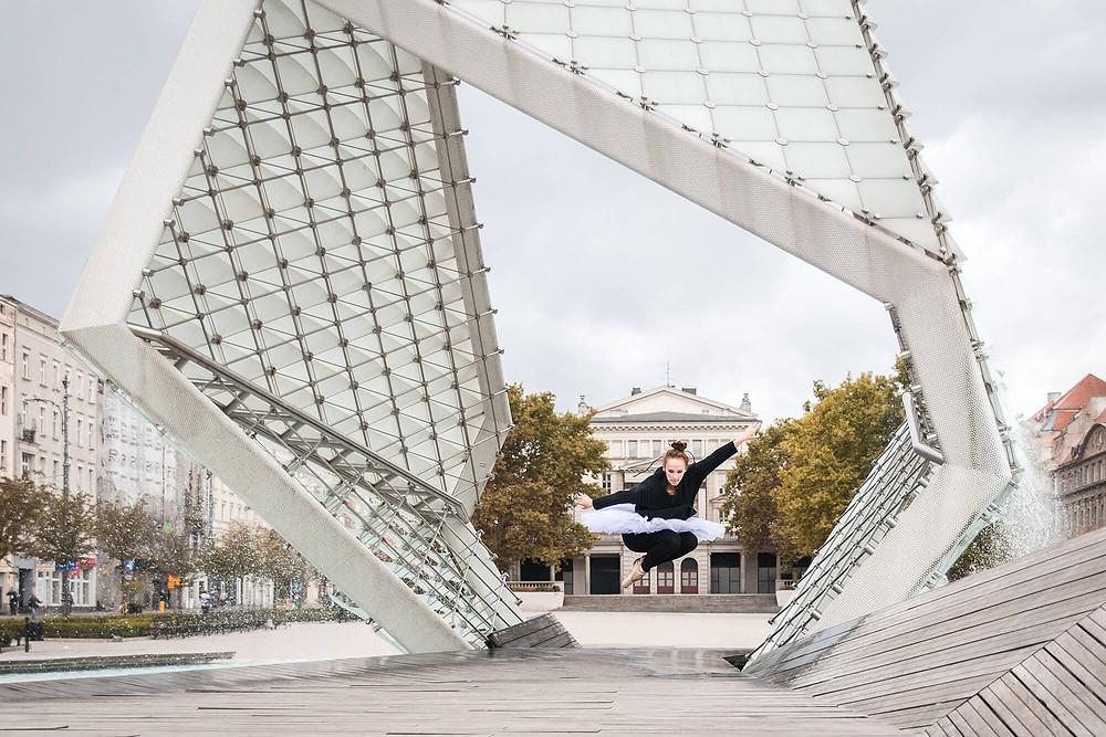 Tancerka w paczce skacze z nowoczesną fontanną w tle