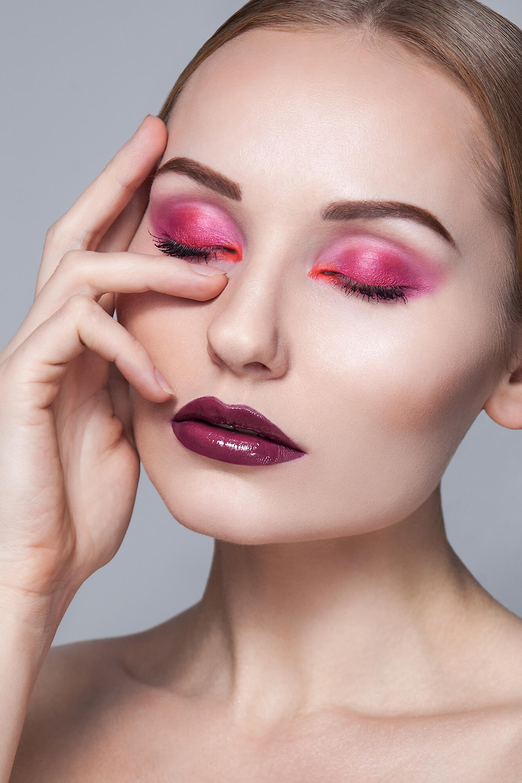 Modelka z idealną cerą i różowym makijażem pozuje z zamkniętymi oczami