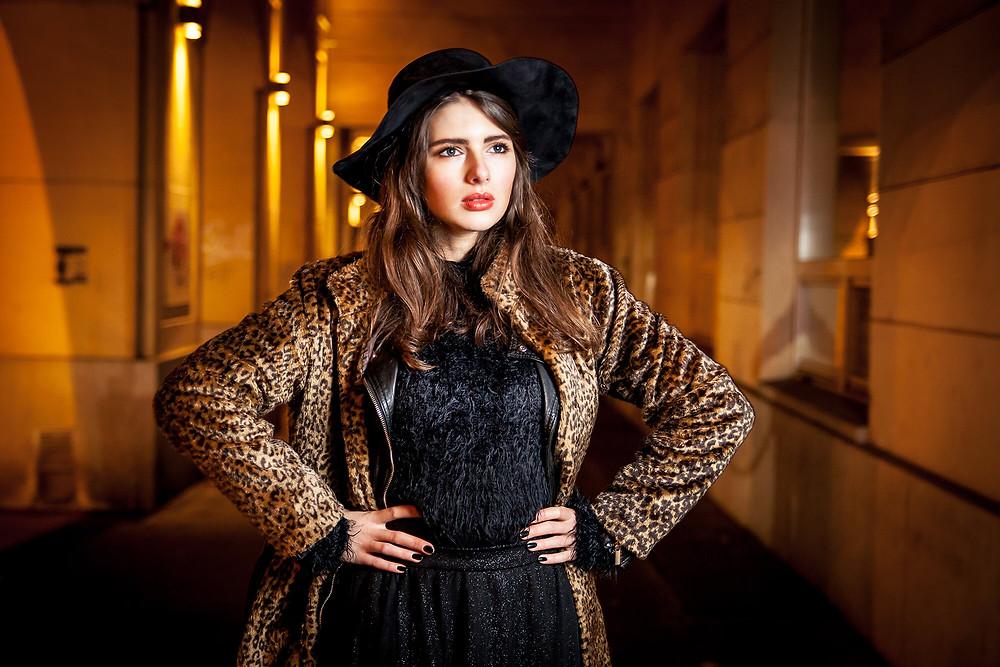 Modelka zapatrzona w dal pozuje w czarnym kapeluszu i płaszczu w panterkę