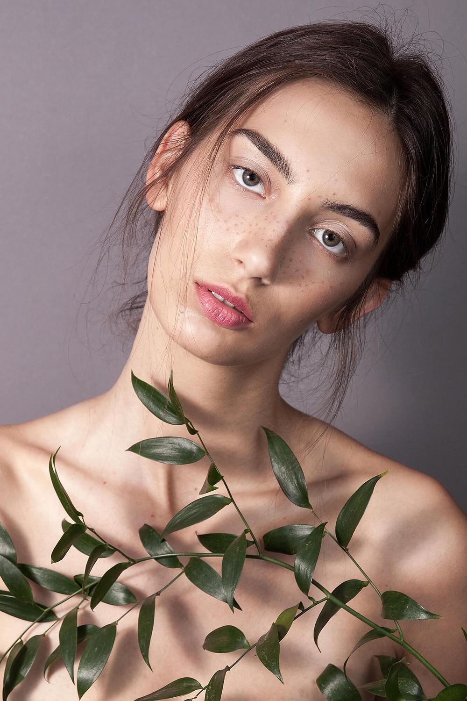 Piękna modelka o oryginalnej urodzie, studyjne zdjęcie beauty z liśćmi