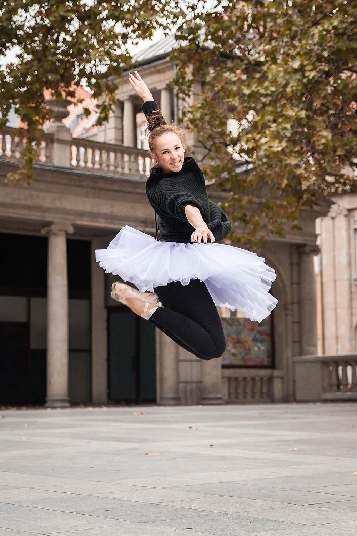 Radosna tancerka w baletowej paczce skacze na tle zabytkowego budynku