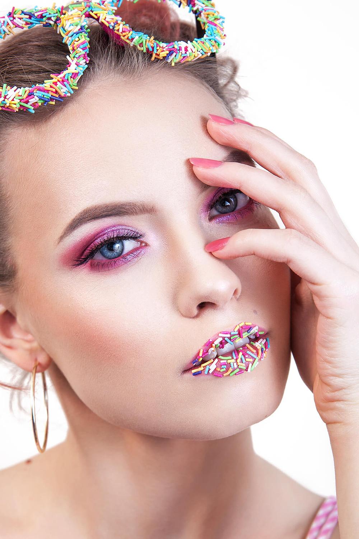 Błękitnooka modelka w różowym makijażu z cukrową posypką na ustach