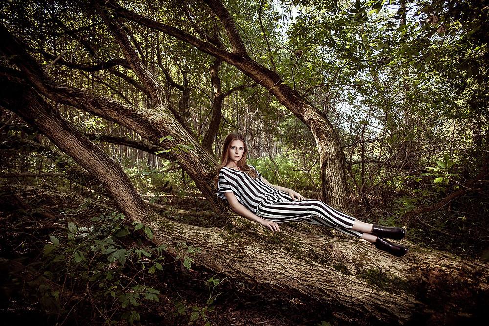 Oryginalna sceneria do sesji zdjęciowej, modelka leży na powalonym drzewie