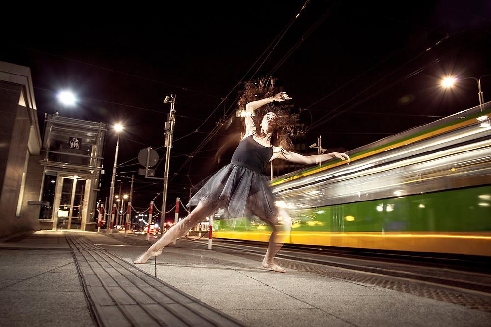 Dynamiczne zdjęcie tancerki z rozmytym tramwajem w tle