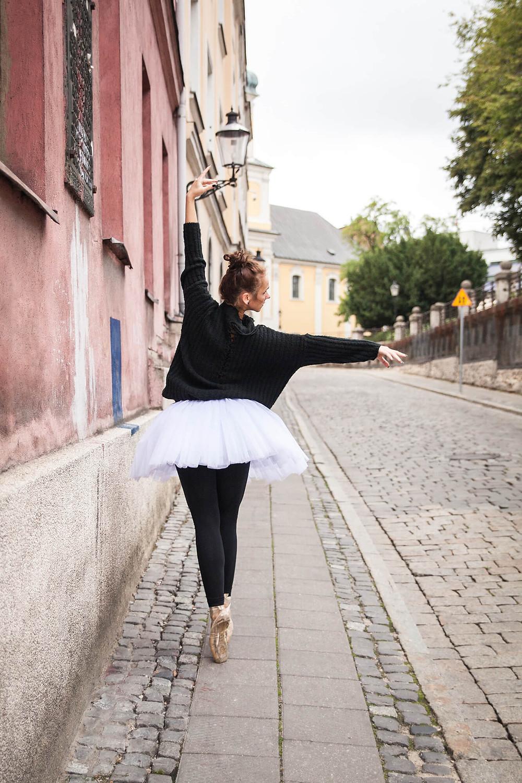 Baletnica stoi na pointach na tle zabytkowej ulicy w Poznaniu