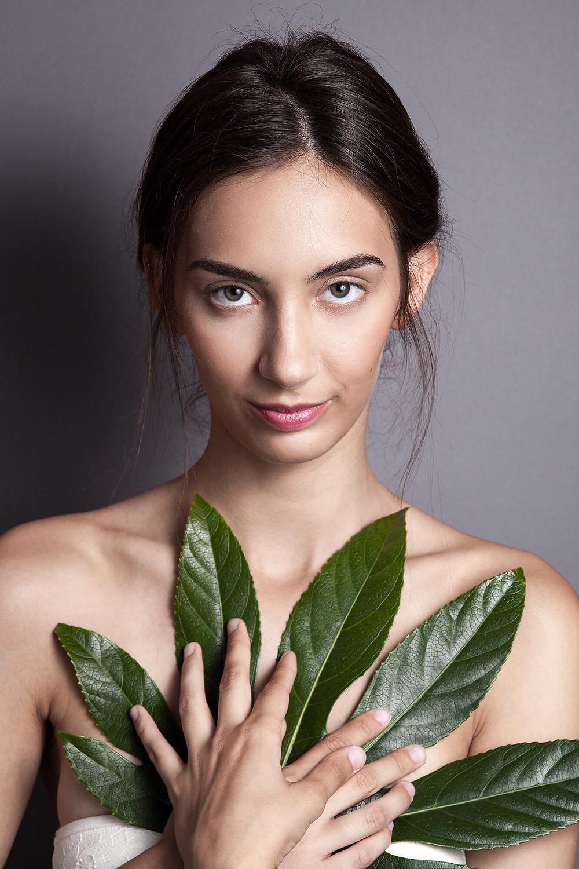 Ciemnowłosa modelka pozuje z dużym, cielonym liściem
