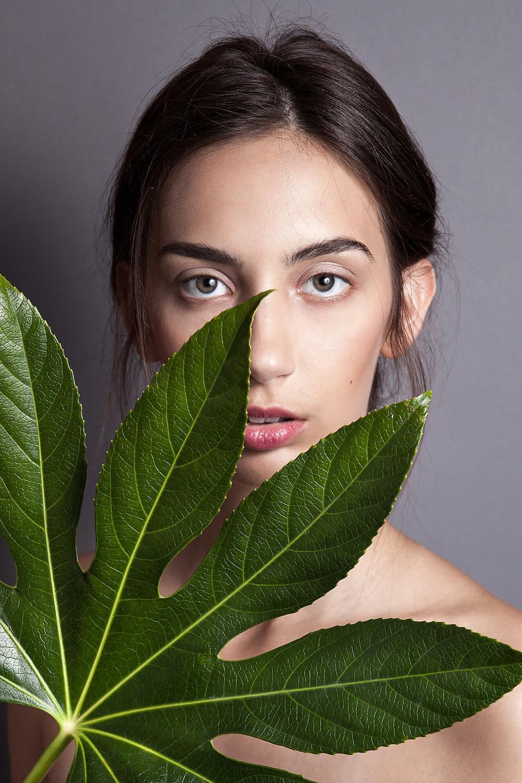Portret modelki bez makijażu przysłoniętej dużym, zielonym liściem
