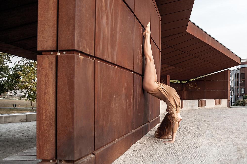 Tancerka w beżowym body stoi na rękach przy blaszanej konstrukcji nad Wartą