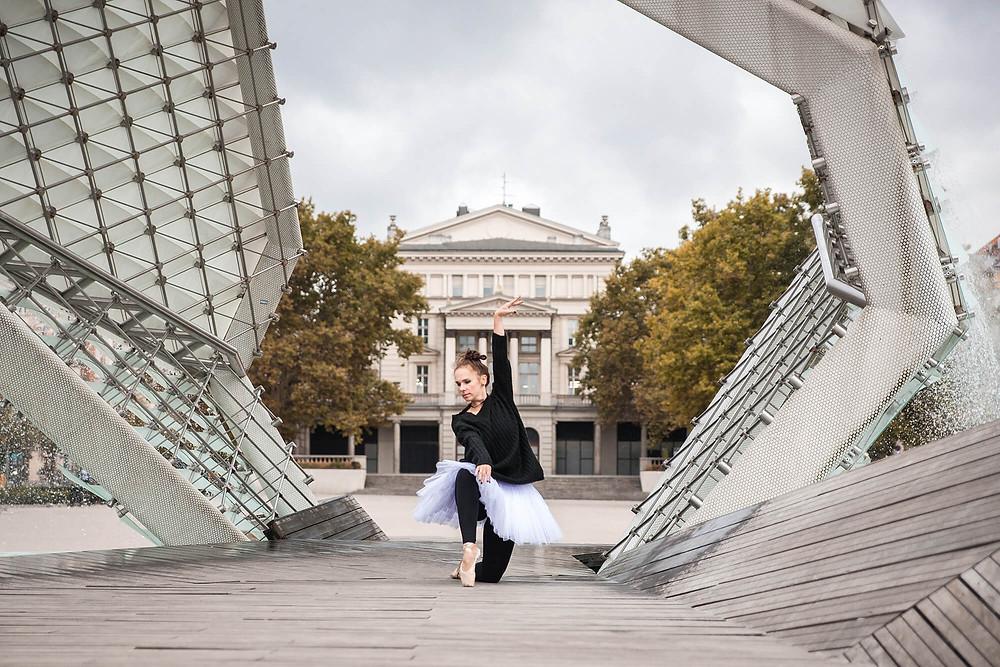 Sesja zdjęciowa tancerki baletu na tle współczesnej fontanny