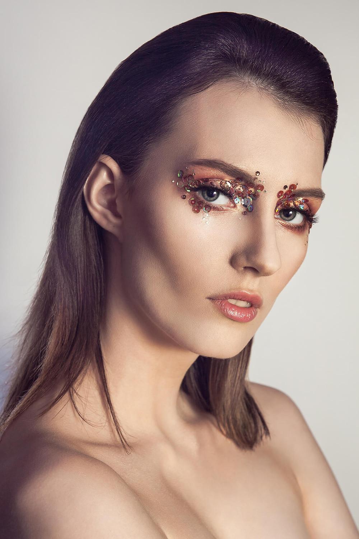 Modelka podobna do Anji Rubik w sesji beauty ze złotymi cekinami
