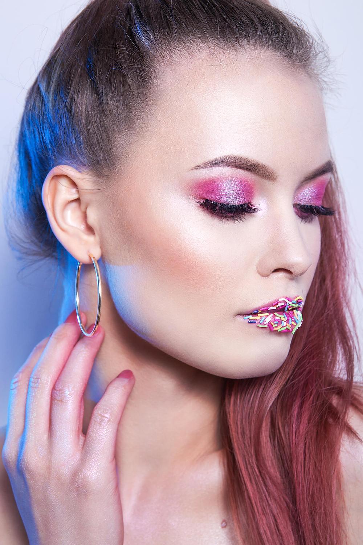 Modelka o nieskazitelnej cerze w różowym makijażu, niebieskie światło konturowe