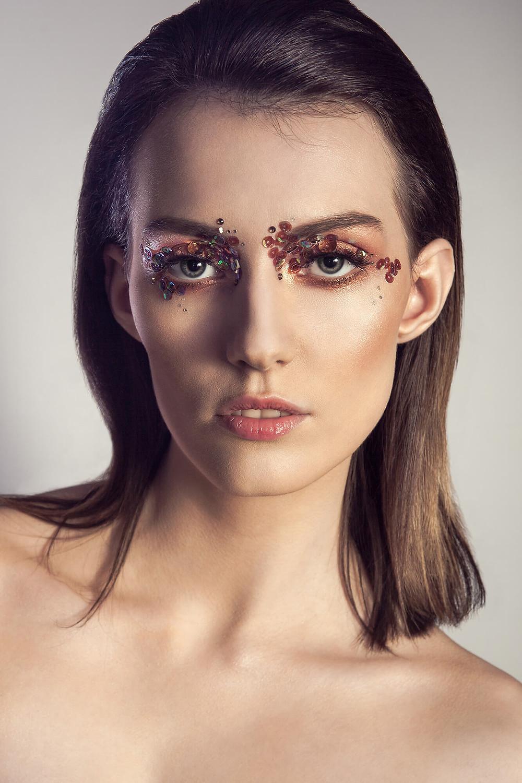 Portret beauty en face, złoty makijaż i cekiny