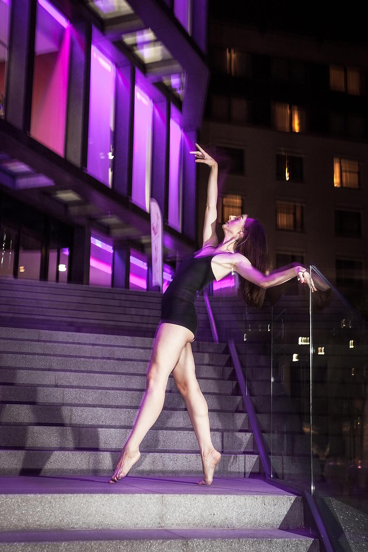 Tancerka stoi na palcach na tle oświetlonego nocą budynku