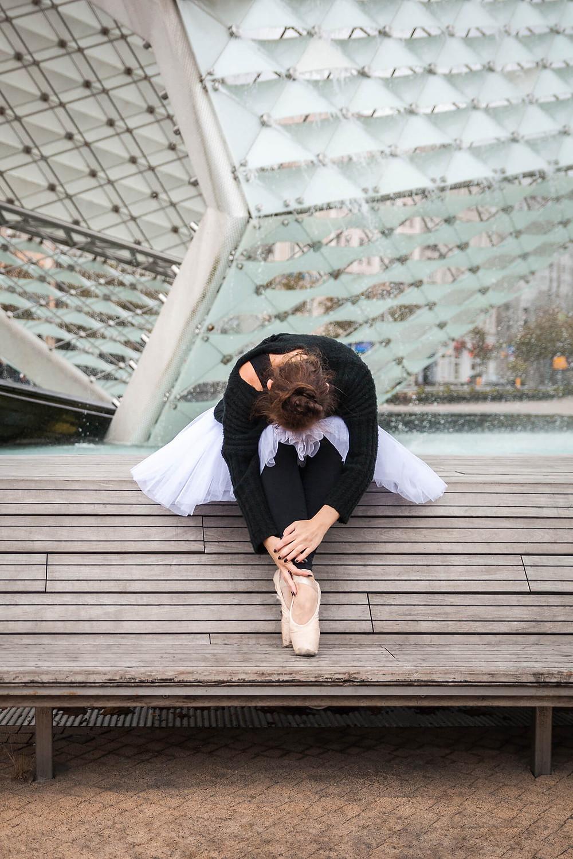 Baletnica w pointach siedzi przy fontannie