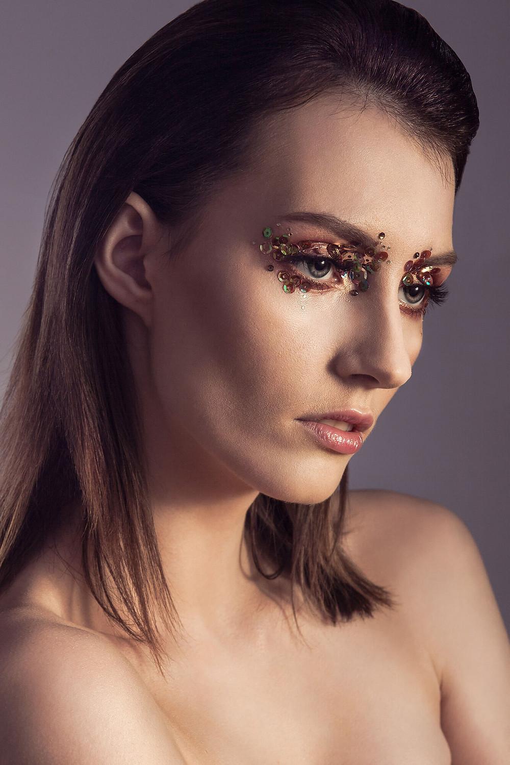 Zamyślona modelka w makijażu z cekinami
