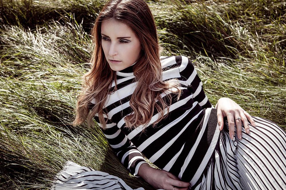 Modelka w golfie i spódnicy w pasy leży w trawie patrząc w dal